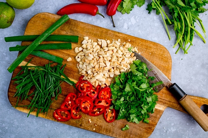 Chopped peanuts, chillies, spring onions and coriander on a board