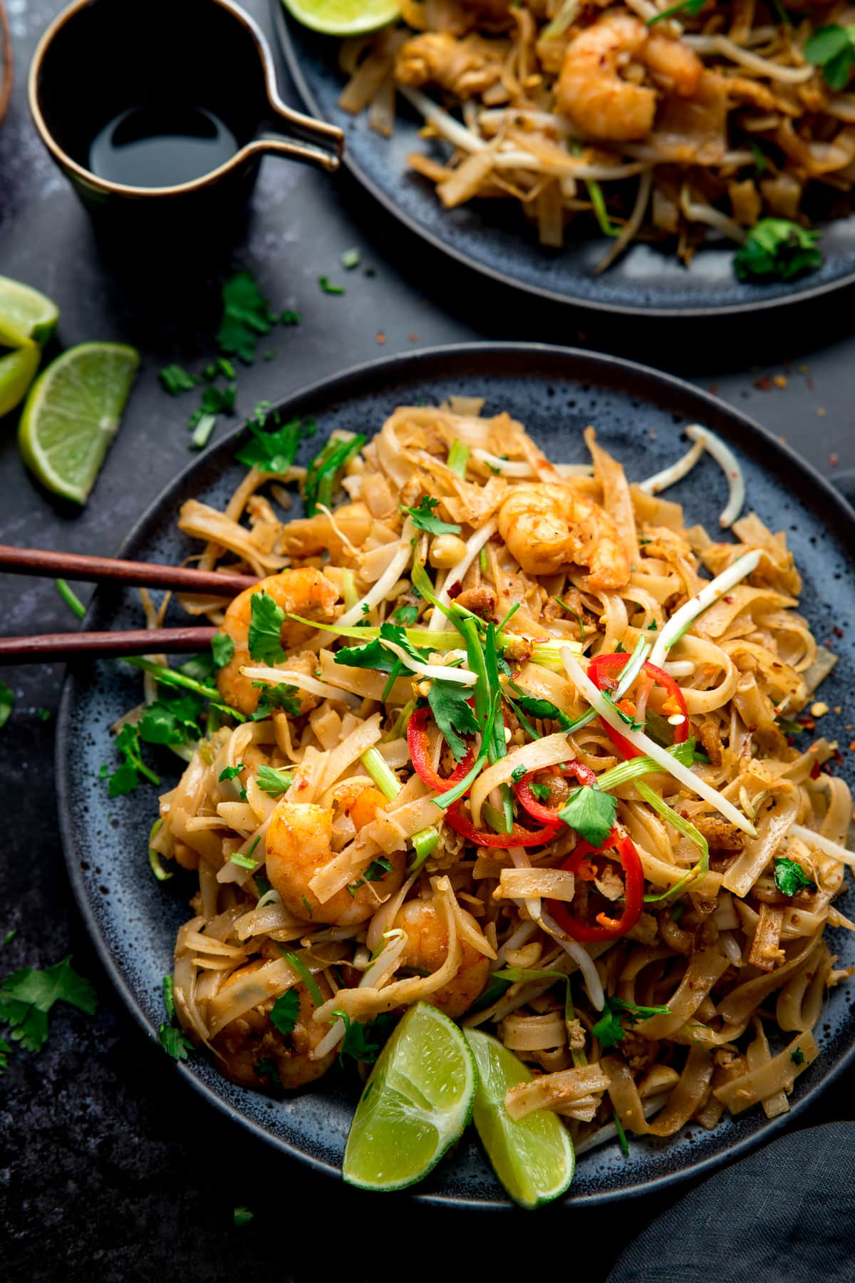 Overhead image of Prawn Pad Thai on a black plate on a black bakcground
