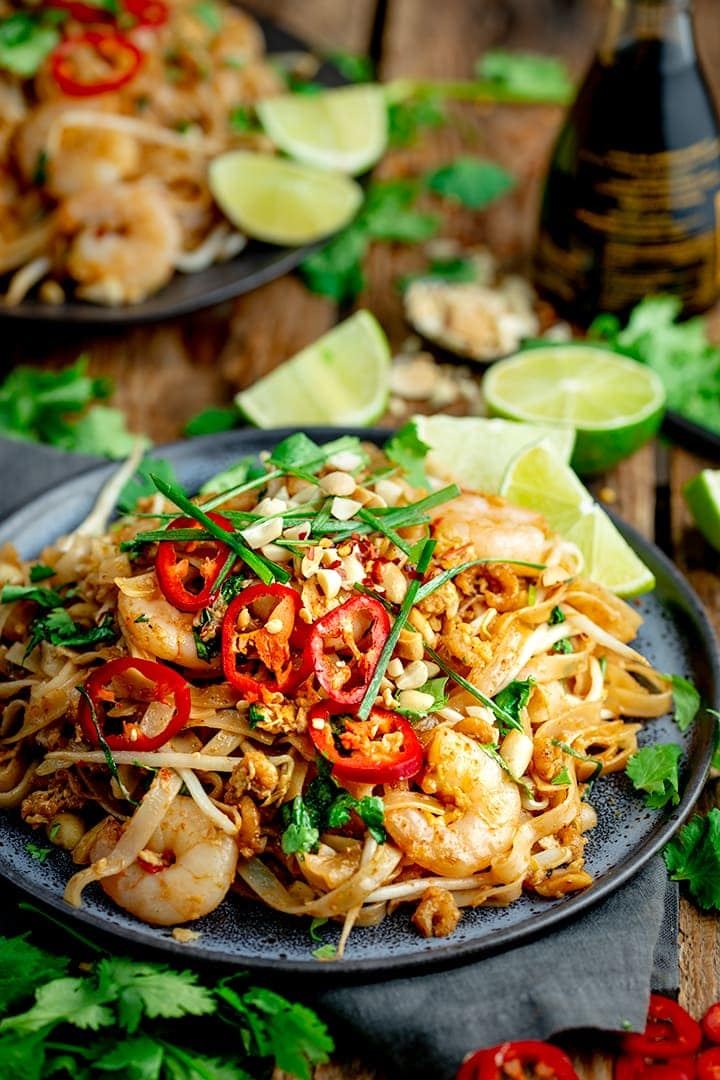Plate of prawn pad thai with ingredients scattered around