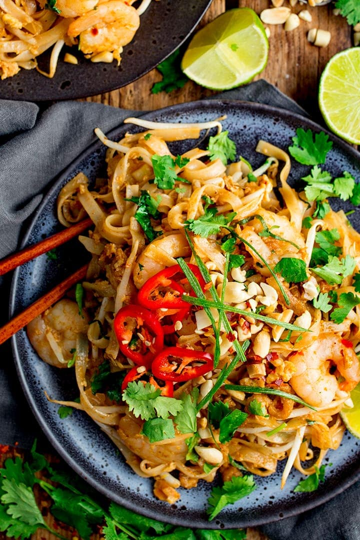 Plate of shrimp pad thai with ingredients scattered around