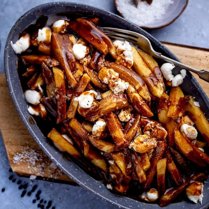 Poutine in a grey dish on a wooden board