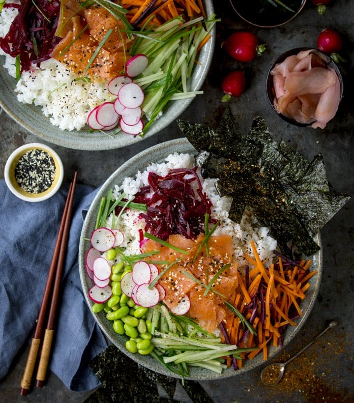 Overhead image of a salmon sushi bowl with a blue napkin and wooden chopsticks