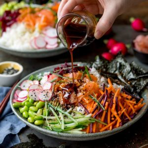 Pouring soy dressing on a sushi salmon bowl