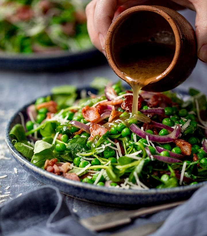 Dressing being poured onto a bacon and pea salad