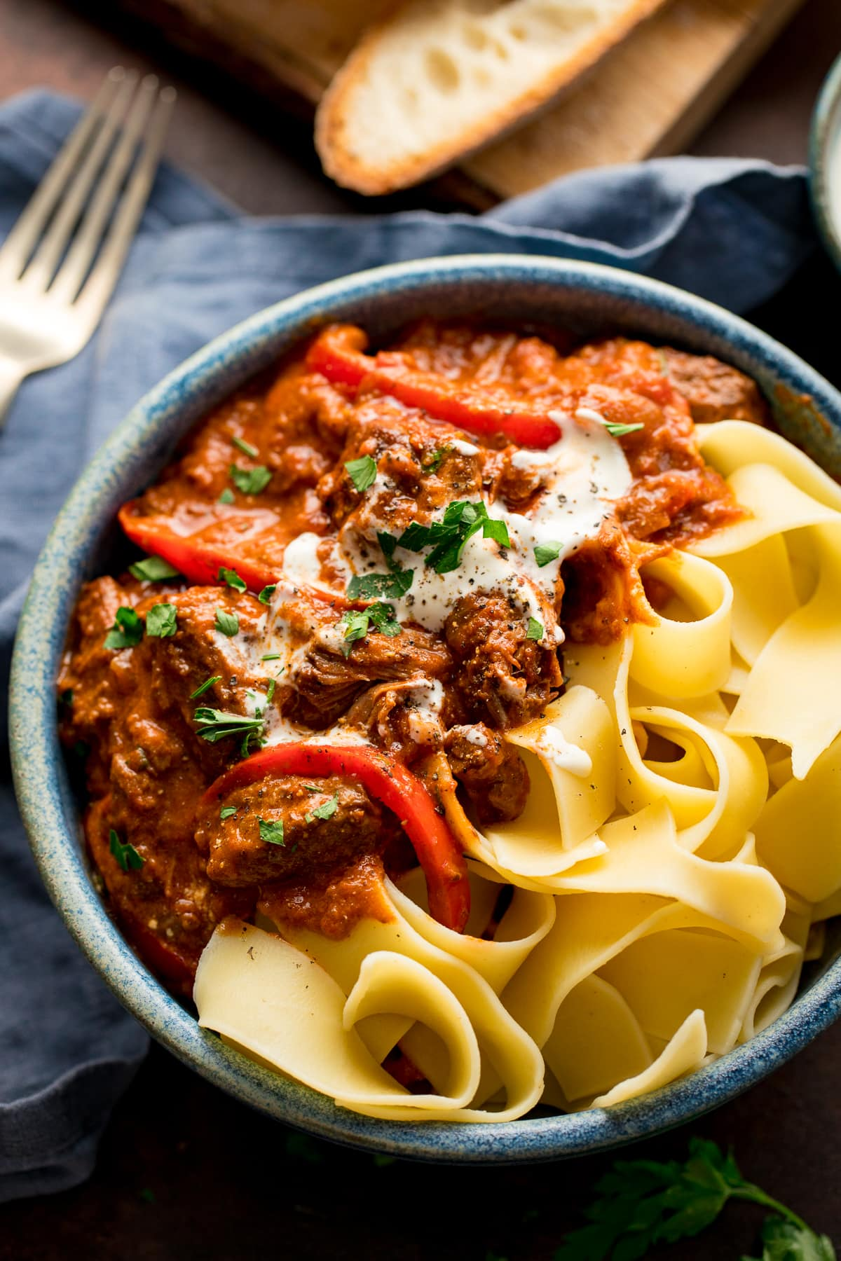 Beef Goulash in a blue bowl with pappadelle pasta