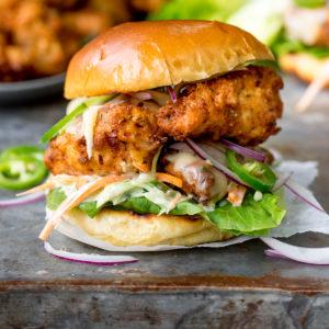 Square image of Crispy chicken burger on a brioche bun with lettuce.
