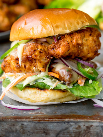 Square image of Crispy chicken burger on a brioche bun with lettuce.