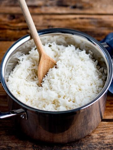 Wooden spoon in a pan of boiled rice