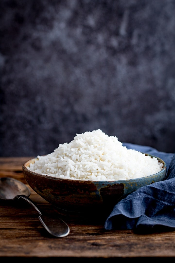 Boiled rice in a bowl on a wooden table