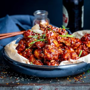 Crispy Korean chicken in a blue bowl on a dark background
