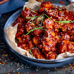 Bowl of Korean fried chicken topped with sesame seeds and strips of spring onion.