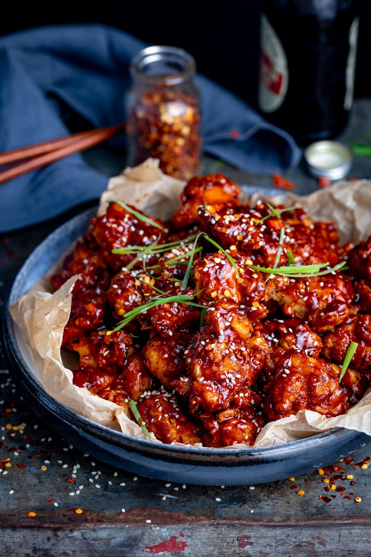 Korean fried chicken in a blue bowl lined with paper. Napkin, chopsticks and jar of chilli flakes in the background.