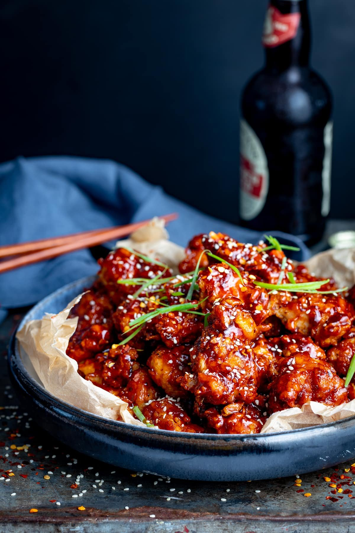 Korean fried chicken in a blue bowl against a dark background. Dark bottle and chopsticks in the background.