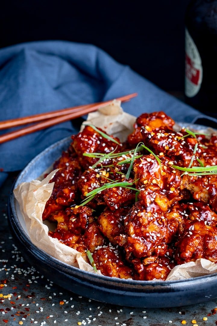 Crispy Korean chicken in a bowl on a dark background