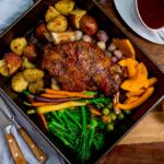 roast lamb shoulder and vegetables in a roasting tin with jug of gravy