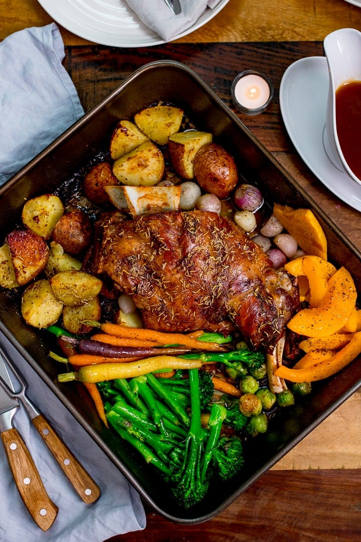 Roast lamb shoulder and vegetables in a roasting tin on a wooden table.