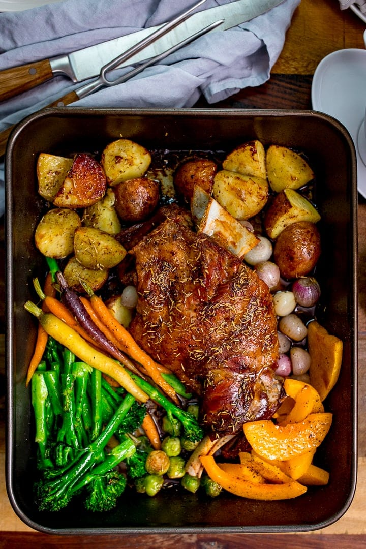 roast lamb shoulder and vegetables in a roasting tin with carving knife