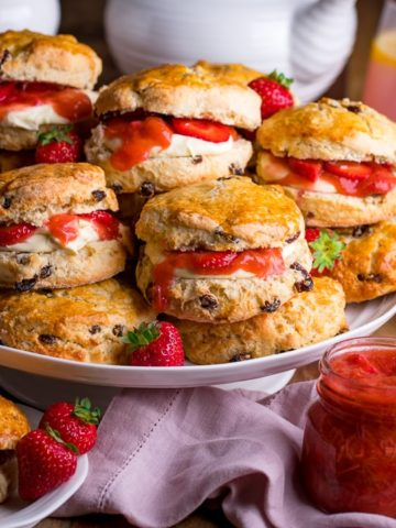 Piled up scones on a white cake stand with jar of rhubarb and strawberry compote