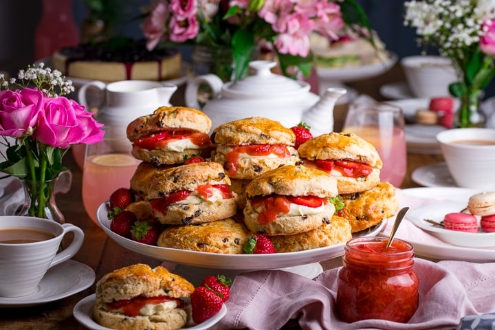 Piled up scones on a white cake stand on a wooden table. Jar of rhubarb and strawberry compote.
