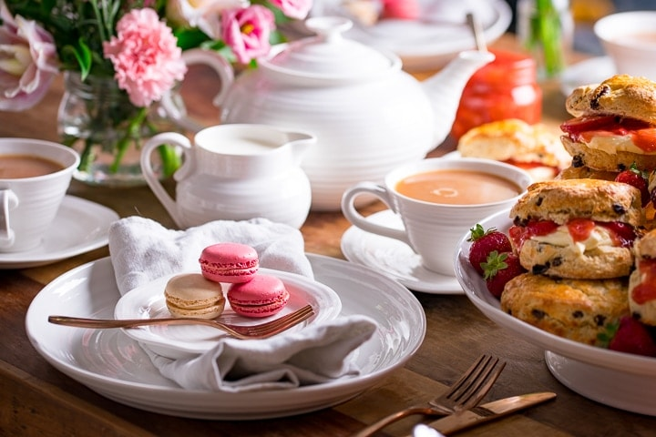 Image of white plates, teapot and milk jug on a table for afternoon tea. Macarons and scones on plates.