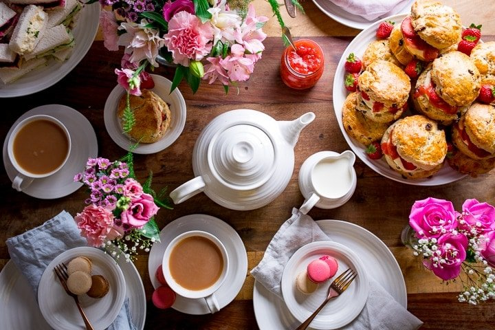 Overhead image of afternoon tea table with scones, flowers, tea and teapot on a wooden table.