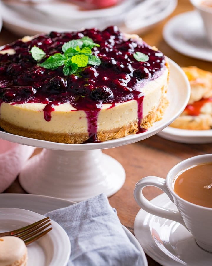 Blueberry cheesecake on a white cake stand on a wooden table