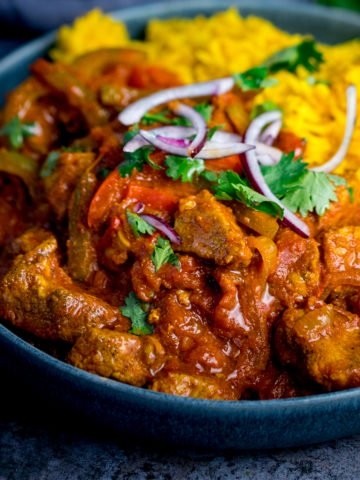 Close up image of chicken Jalfrezi with pilau rice in a blue bowl