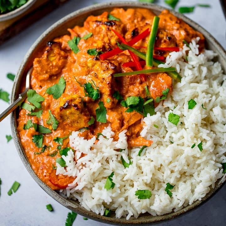 Bowl of chicken tikka masala with rice on a light background