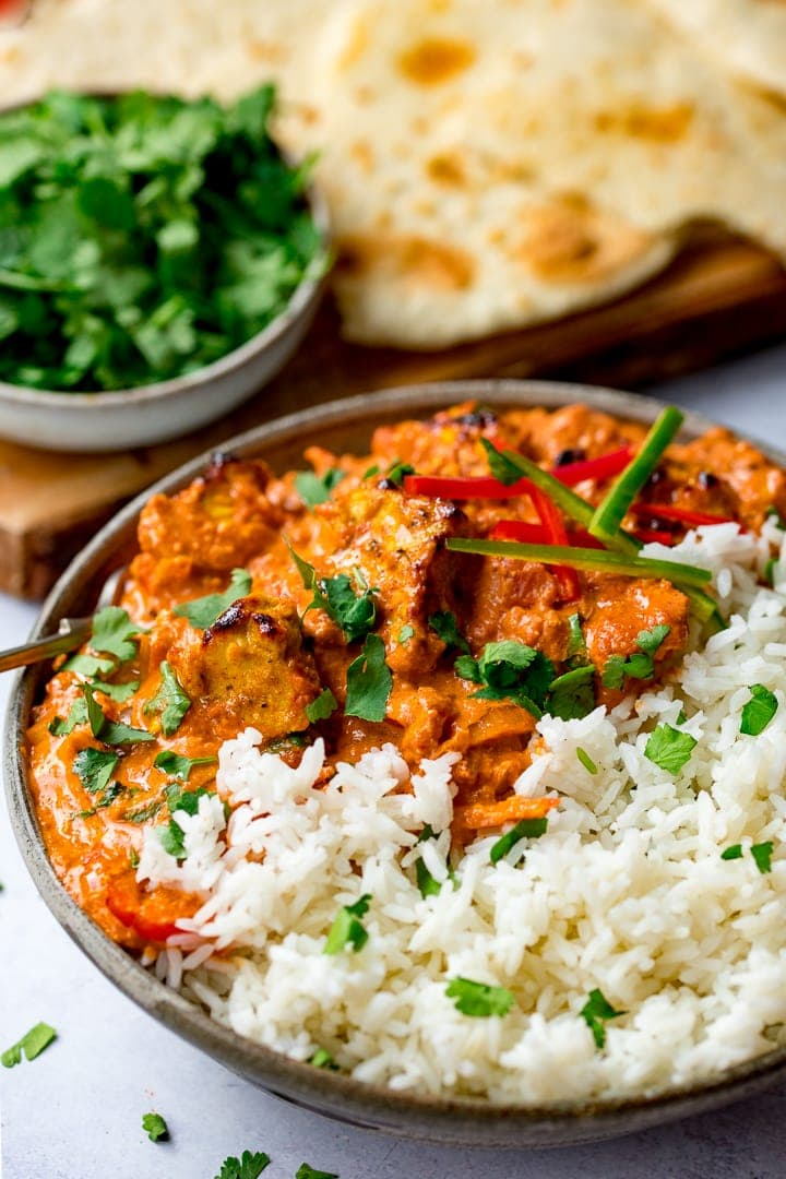Bowl of chicken tikka masala with rice and flatbreads