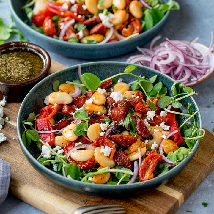 Chorizo and Lima Bean Salad in a bowl on a wooden board