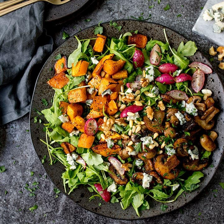 Garlic mushroom and roasted squash salad on a dark plate on a dark background