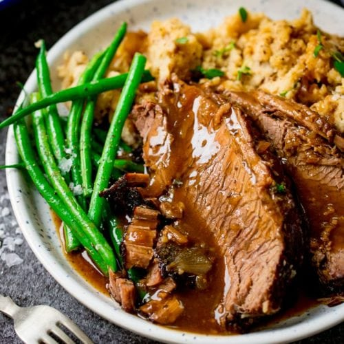 plate of sliced beef, vegetables and gravy on a dark background