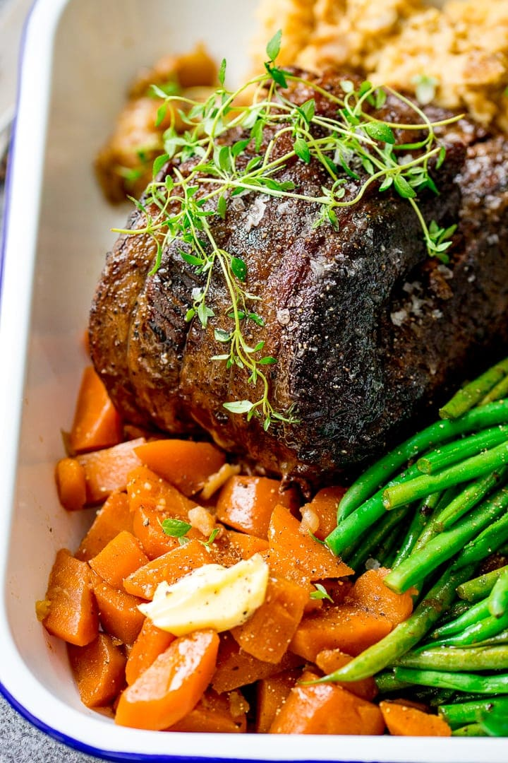 Pot roast beef and vegetables in a white serving dish