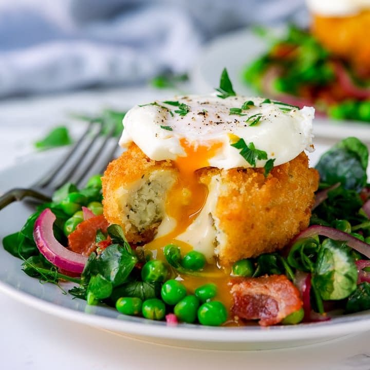 pea and bacon salad topped with a fish cake and poached egg that have been cut into.