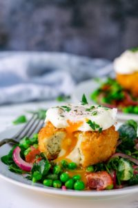 pea and bacon salad topped with a fish cake and poached egg on a light background