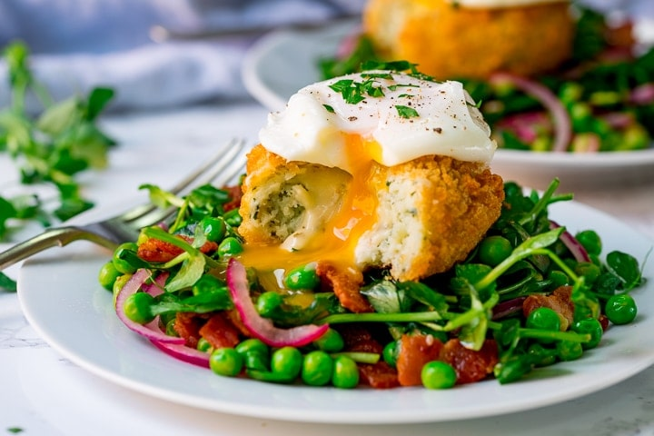 Wide image of pea and bacon salad topped with a fish cake and poached egg - which have been cut into