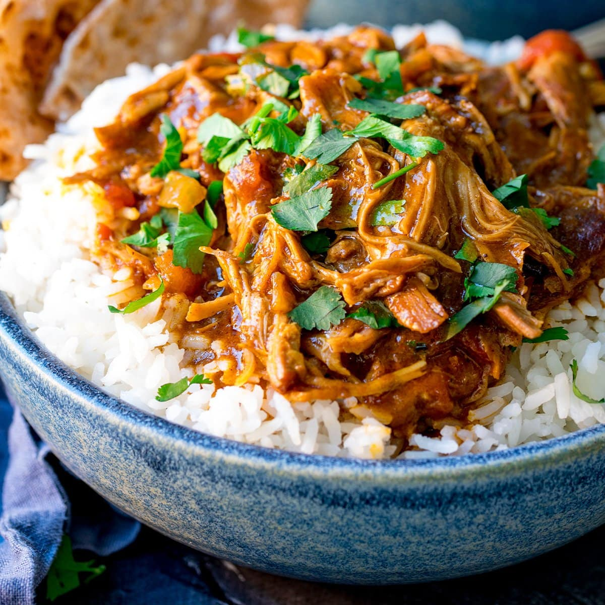 Close up picture of slow Cooked Pulled Lamb Curry on a bed of boiled rice in a blue bowl