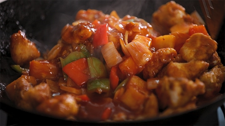 Close up image of sweet and sour chicken in a wok