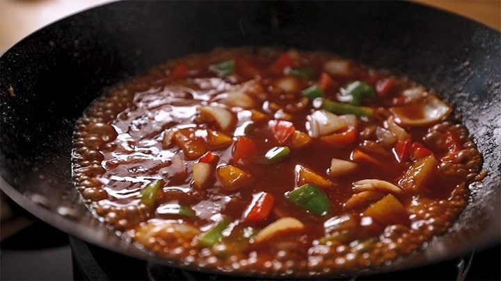 Sweet and sour sauce with vegetables bubbling in a wok