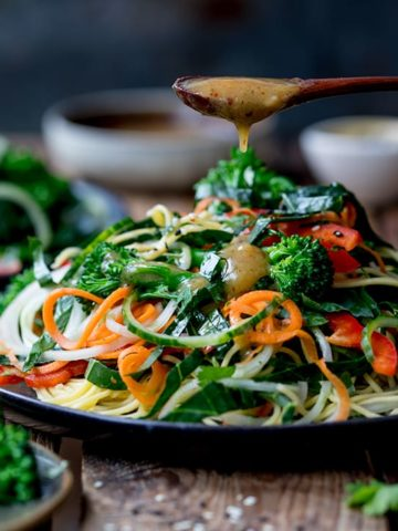 miso dressing being drizzled onto a noodle salad on a dark background