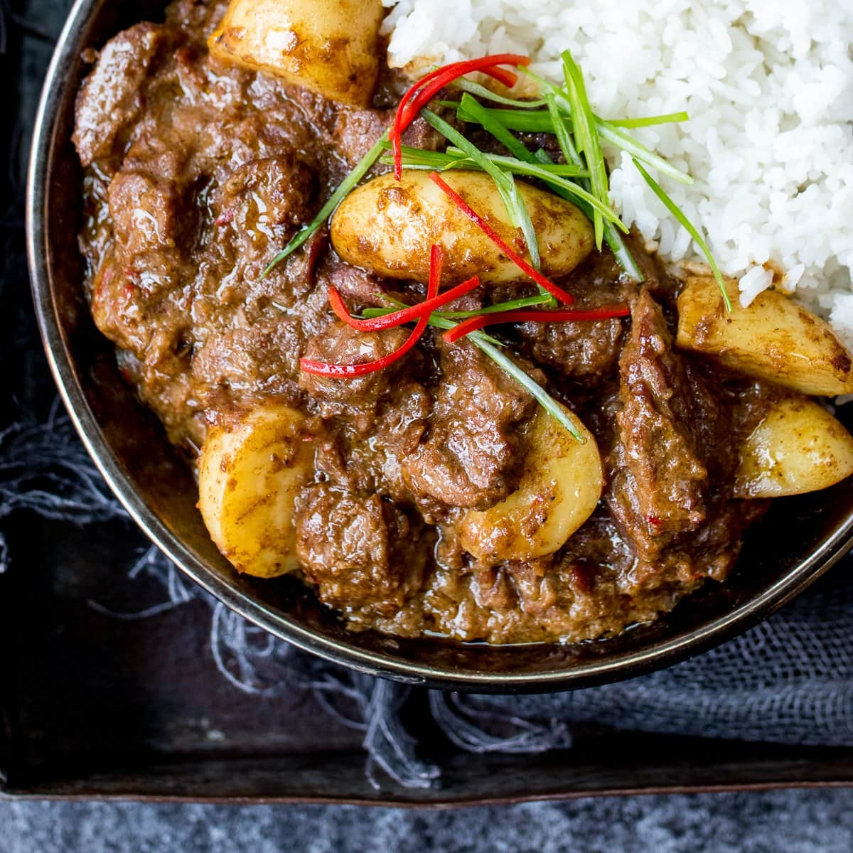 A bowl of beef massaman curry with rice on a dark background
