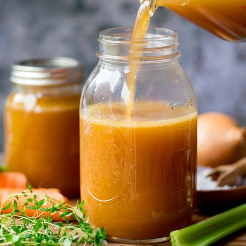 Chicken stock being poured into a glass jar