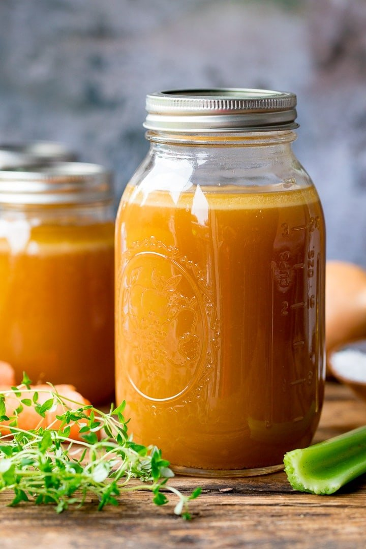 Glass mason jar filled with chicken stock on a wooden board