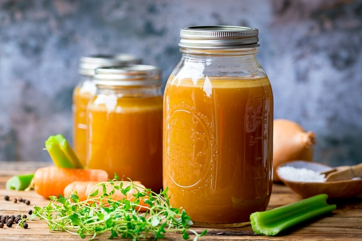 3 jars of chicken stock on a wooden board with vegetables around