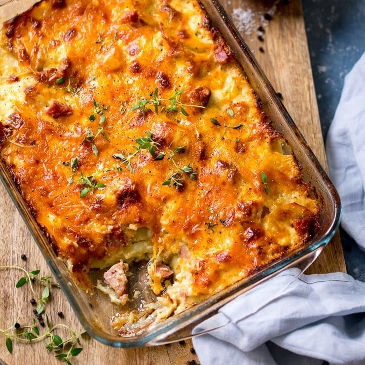 Scalloped potatoes with ham in a dish, with a scoop taken out