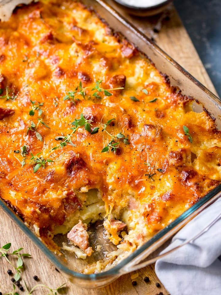 Scalloped potatoes with ham in a baking dish, scoop removed