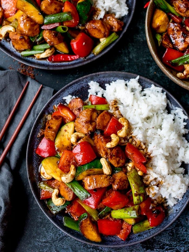 Kung pao chicken on a dark plate with rice