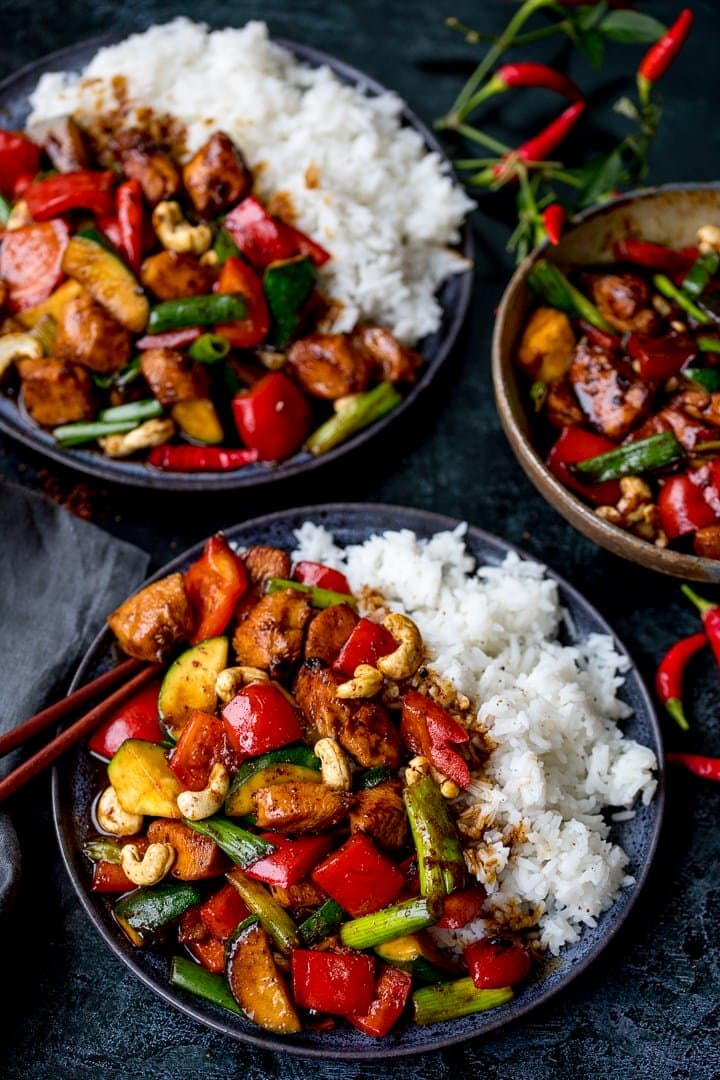 Two plates of kung pao chicken with rice