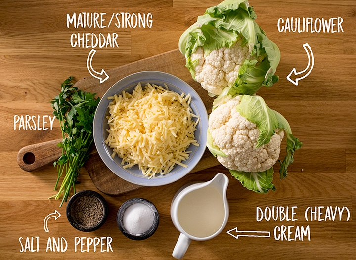 Ingredients for cauliflower cheese on a wooden table