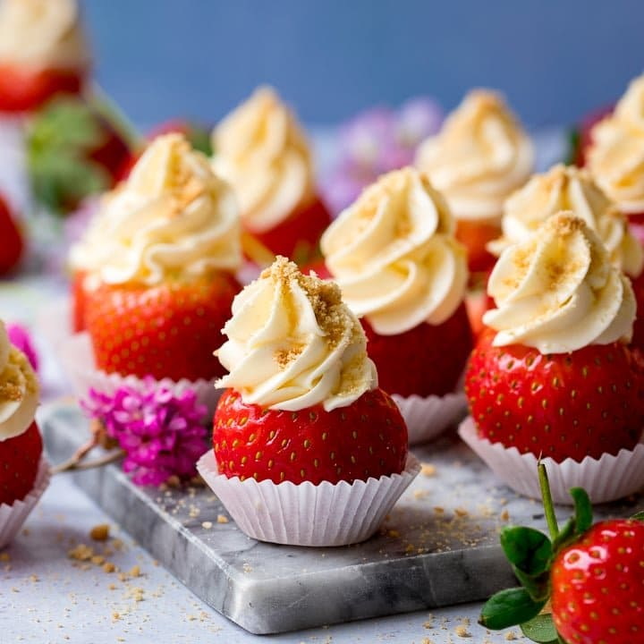 Cheesecake stuffed strawberries on a marble chopping board